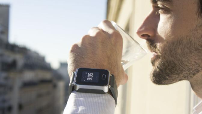 Diapo 3 : Personne portant une montre K'track Glucose au poignet gauche, buvant un verre d'eau.