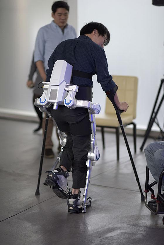 Diapo 3 : Personne se déplaçant grâce à l'exosquelette H-MEX en intérieur.