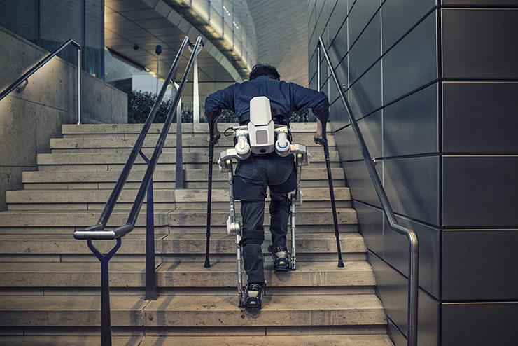 Diapo 2 : Personne montant des escaliers grâce à l'exosquelette H-MEX.