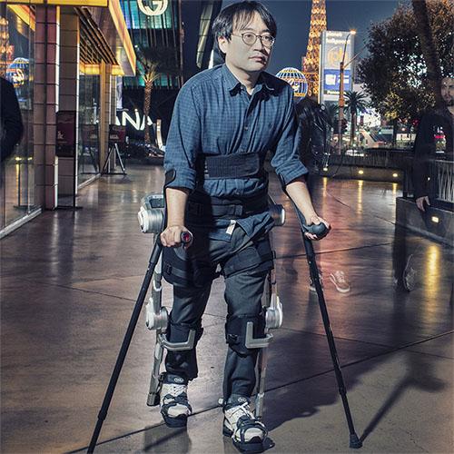 Diapo 1 : Personne se déplaçant grâce à l'exosquelette H-MEX en extérieur.