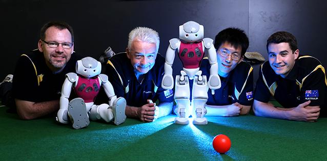 Diapo 3 : 4 Personnes allongées sur le sol, avec deux robots Naos et une balle rouge.
