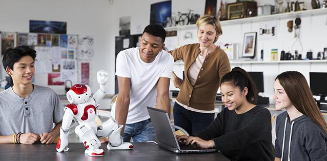 Diapo 4 : Un robot NAO dansant sur une table, face à 5 personnes souriant, dont une utilisant un ordinateur portable