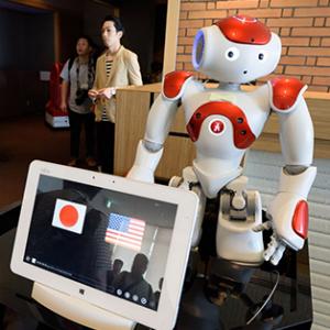 Robot Nao, sur une table à coté d'un ordinateur affichant les drapeau Américains et Japonais.