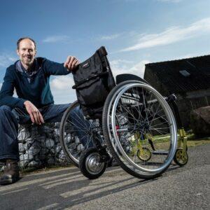 Homme assis à côté d'un fauteuil roulant qui dispose de la roue forcewheel