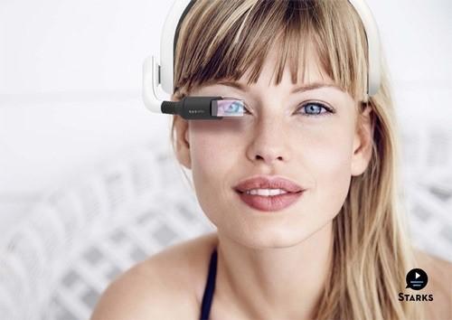 Diapo 2 : Gauche de l'image: Logos des application Greta et Starks, légende: 'Profitez enfin du cinéma'. Droite de l'image: Personne de face portant un casque Greta & Straks, composé d'écouteurs et d'un mini écran devant l'œil droit.