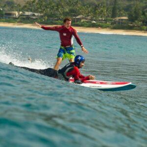 Homme handicapé des jambes qui fait du surf couché sur le ventre, avec derrière un autre homme qui surfe debout