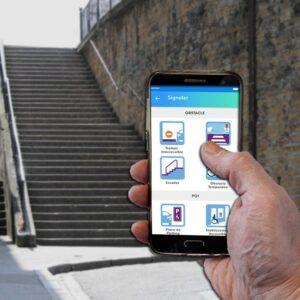 Personne utilisant l'application StreetCo sur un smartphone qui lui indique la présence d'escaliers en face d'elle