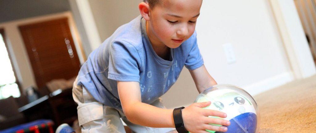 Diapo 3 : Un enfant, assit sur le sol, jouant avec deux robots leka et une tablette.