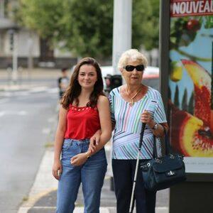 Photo d'une personne non-voyante tenant le bras d'une personne voyante dans la rue