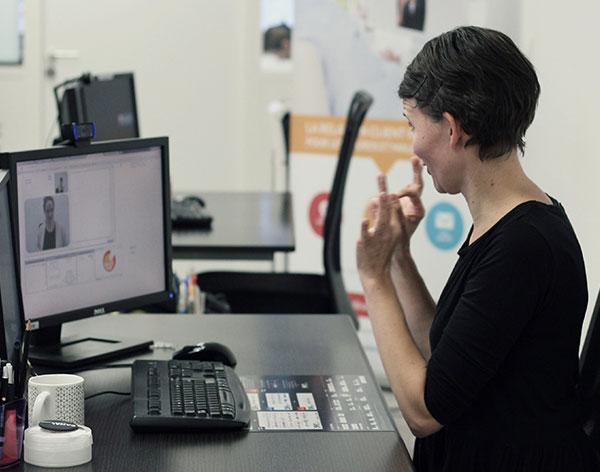 Diapo 5 : Femme qui signe en utilisant Sourdline devant un ordinateur