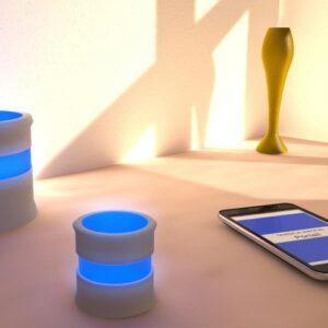 Photo d'un smartphone coupée au dispositif Smartear allumé d'une couleur bleue pour signifier qu'il y a quelqu'un au portail