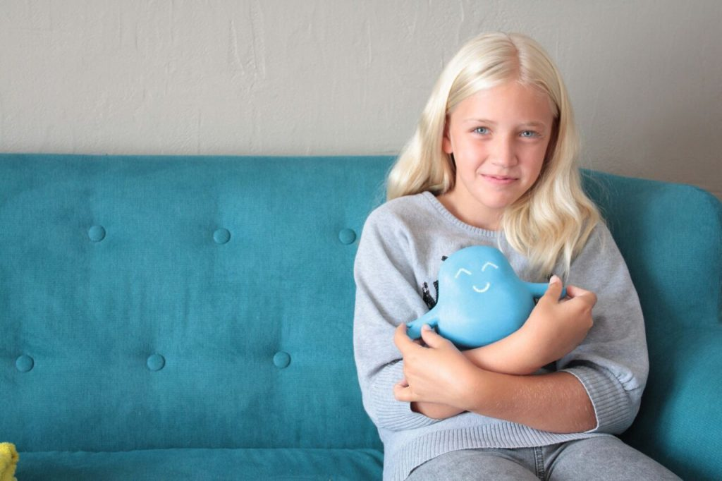 Diapo 2 : photo représentant une jeune fille avec dans ses bras le robot meyko