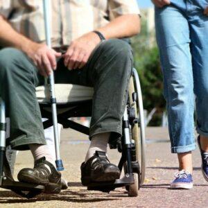 Photo de deux personnes qui se baladent dont une en fauteuil roulant