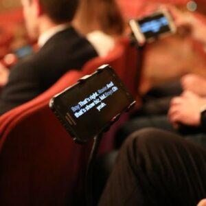 Image avec des personnes au théâtre utilisant l'application Galapro sur leur smartphone