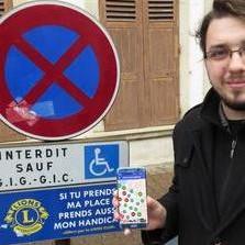 Homme devant une place réservée aux personnes handicapées montrant l'application Stationnement Handicapé sur son téléphone