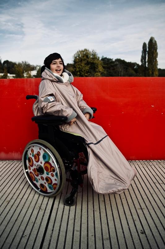 Diapo 3 : Fille en fauteuil roulant portant sur elle un vêtement adapté de la marque Les loups bleus