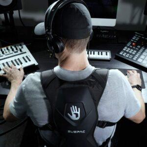 Photo d'un homme en studio de musique avec un casque sur les oreilles et le gilet Subpac