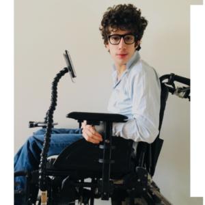 Homme assis dans un fauteuil roulant où le bras handieasy y est accroché