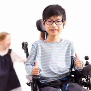 Garçon en fauteuil roulant portant sur elle un vêtement adapté de la marque Les loups bleus