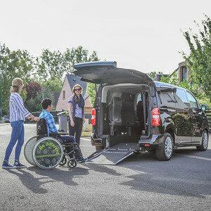Photo d'un véhicule adapté aux personnes en fauteuil roulant avec un homme en fauteuil qui monte dans le véhicule