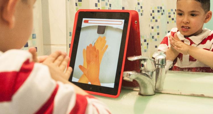 Diapo 3 : Petit garçon qui se lave les mains en regardant sur une tablette comment Ben le Koala fait
