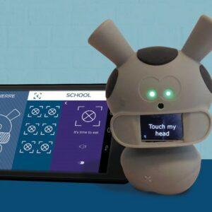 Photo du robot Mwoo avec écrit dessus «touche ma tête», avec derrière l'application sur une tablette