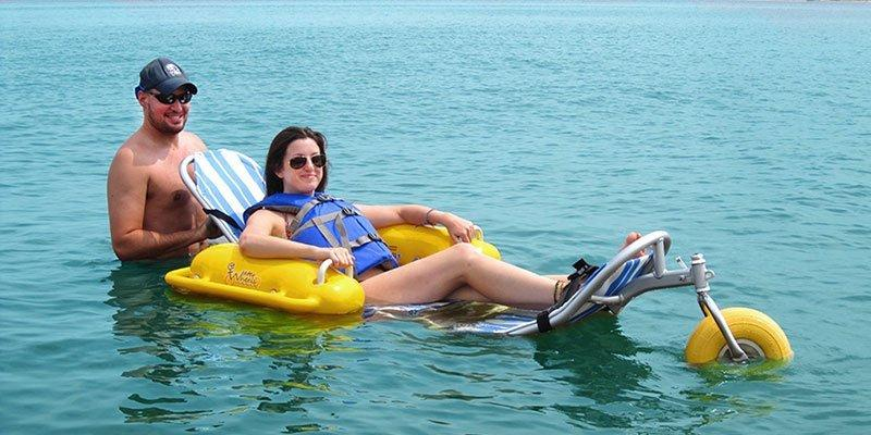 Diapo 3 : Image de deux personnes à la plage dont une handicapée qui est sur un flotteur dans l'eau