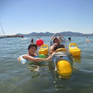 Image de deux filles à la plage dont une handicapée qui est sur un flotteur dans l'eau