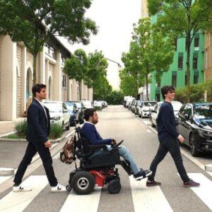 Les trois fondateurs d'Andyamo traversant sur un passage piéton avec Marco tétraplégique en fauteuil roulant