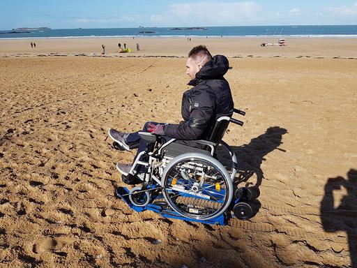 Diapo 6 : photo représentant une personne sur un fauteuil roulant sur du sable