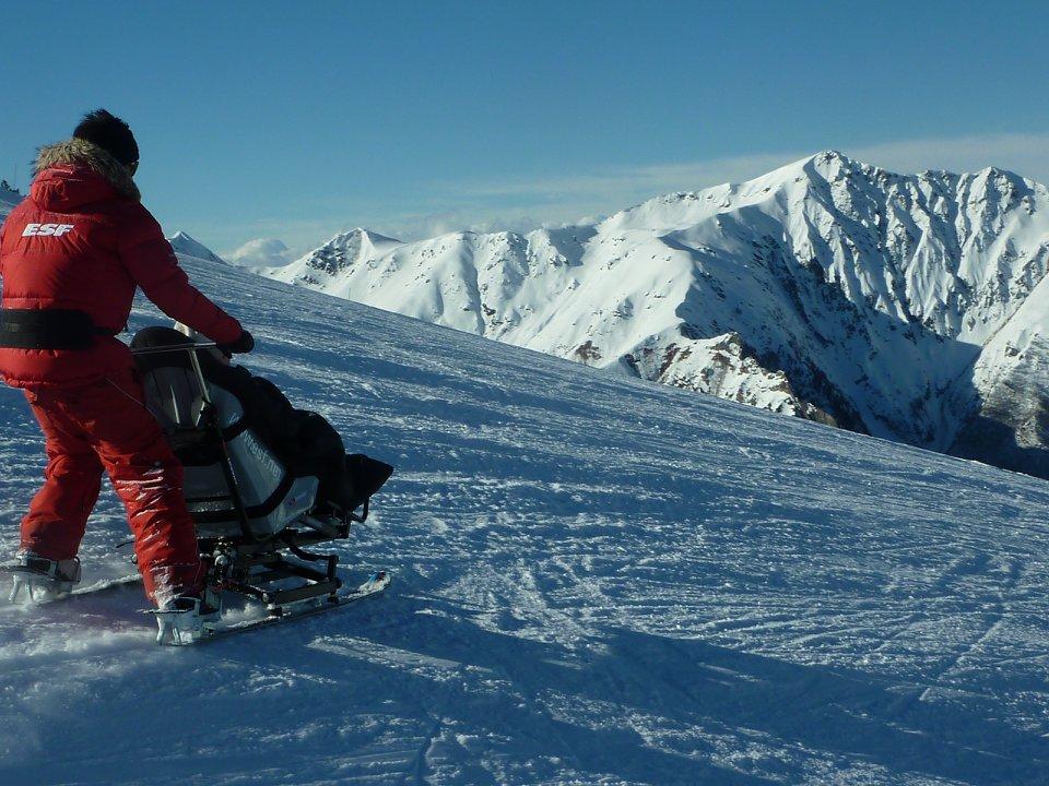 Diapo 3 : Moniteur de ski qui aide une personne à mobilité réduite à skier