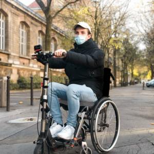 Photo d'une personne en fauteuil roulant accroché à une trottinette par le dispositif globe trotter