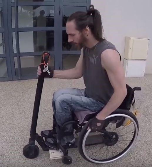 Diapo 3 : photo qui représente un homme utilisant la trotinette electronique avec son fauteuil