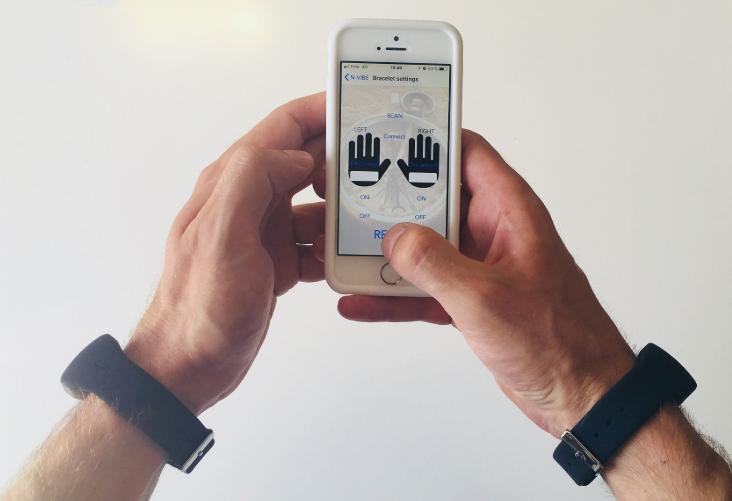 Diapo 3 : mains qui tiennent un téléphone avec l'application N-Vibe