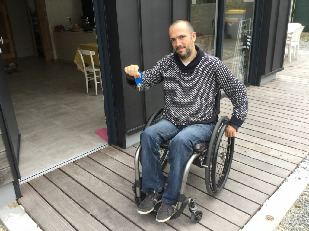 Diapo 3 : Photo d'un homme en fauteuil roulant avec des clés dans la main devant une maison