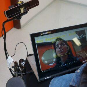 Photo d'une personne utilisant le dispositif Hoobox Robotics qu'elle dirige par ses expressions faciales
