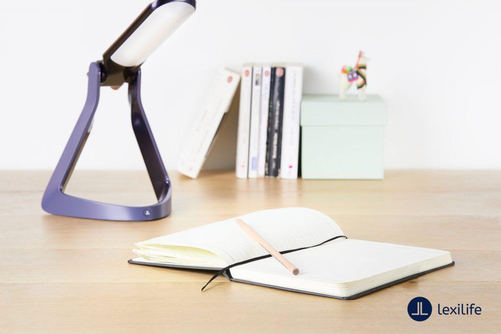 Diapo 3 : photo qui représente la lexilight avec un cahier sur un burea