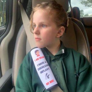 cette image représente une ceinture de sécurité portée par une petite fille avec écrit dessus «j'ai un implant cochléaire»