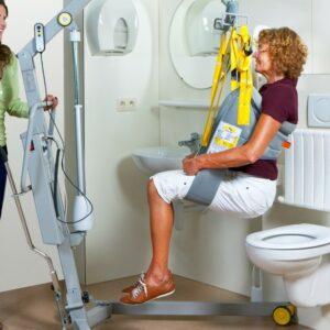 Femme handicapée étant portée par le dispositif Handimov afin de s'asseoir sur le toilette