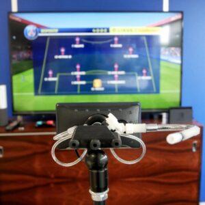 cette image contient l'handi joystick devant un jeu vidéo de football