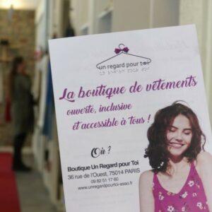 Image de l'intérieur d'un magasin «Un regard pour toi» avec un flyer de la boutique en premier plan