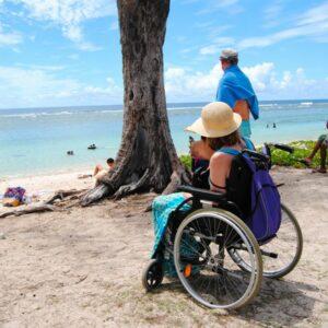 Femme en fauteuil roulant sur le sable au bord d'une plage