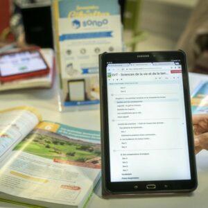 Photo d'une tablette avec l'outil Sondo dessus, et à côté des manuels scolaires