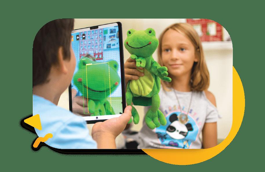 Diapo 7 : Garçon malvoyant qui utilise sa tablette en braille Feelif pour reconnaitre l'objet qu'une petite fille lui montre à l'aide de la caméra de la tablette