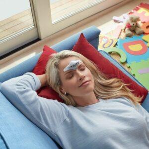 Image d'une femme qui se repose sur un canapé avec le dispositif Cefaly sur son front, on voit des jouets devant en bazar sur le sol