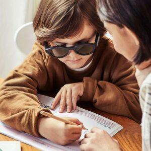 Photo d'un garçon qui écrit tout en portant les lunettes Lexilens