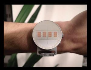 La DotWatch sur le bras d'une personne, les 4 cellules de braille en couleur orange
