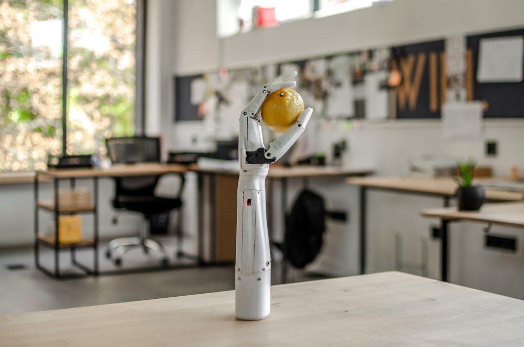 Diapo 3 : La prothèse de main Esper Bionics sur une table avec un citron tenu