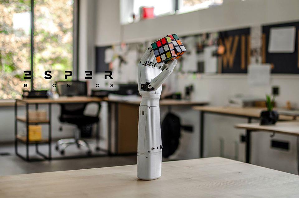Diapo 4 : La prothèse de main développée par Esper Bionics sur une table tenant un Rubik's Cube