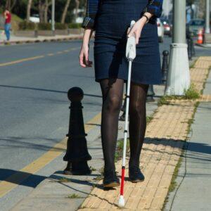 Femme qui marche dans la rue avec la canne blanche We walk